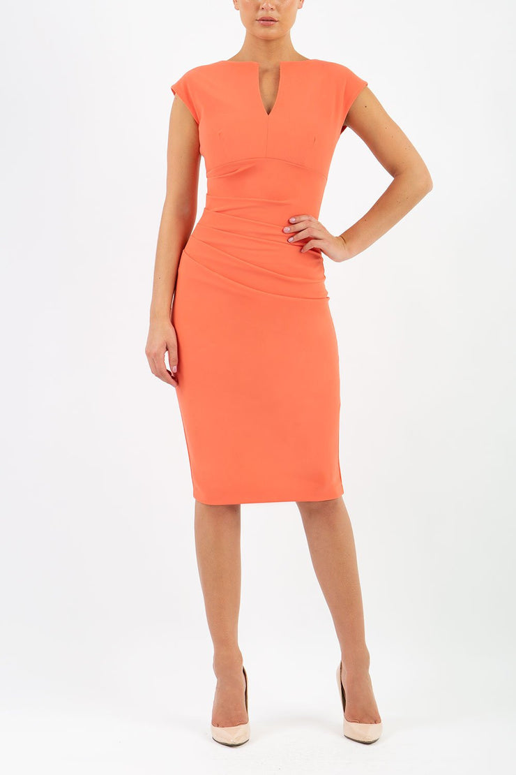 Model wearing Diva Catwalk Lydia Classic Sleeveless Bodycon Pencil Dress rounded neckline with slit in Sea Coral front