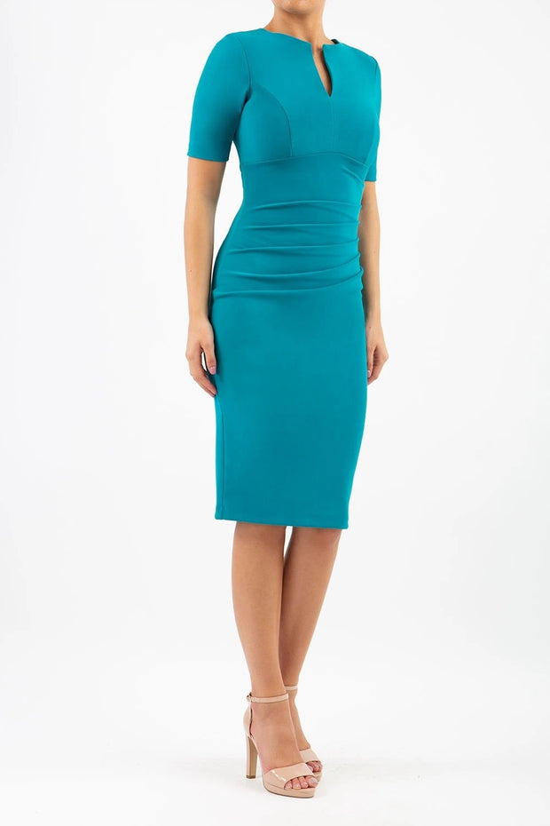 blonde model is wearing diva catwalk lydia short sleeve pencil fitted dress in mosaic blue colour with rounded neckline with a slit in the middle front
