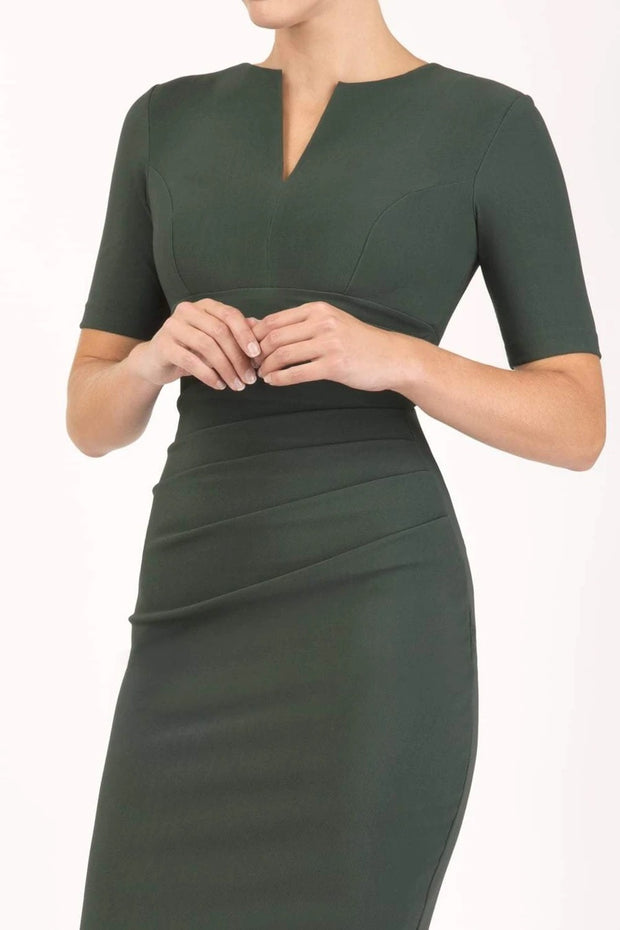 model is wearing diva catwalk lydia short sleeve pencil fitted dress in deep green colour with rounded neckline with a slit in the middle back