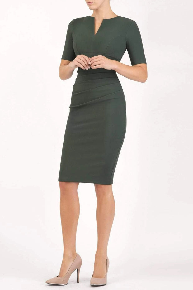 blonde model is wearing diva catwalk lydia short sleeve pencil fitted dress in deep green colour with rounded neckline with a slit in the middle front