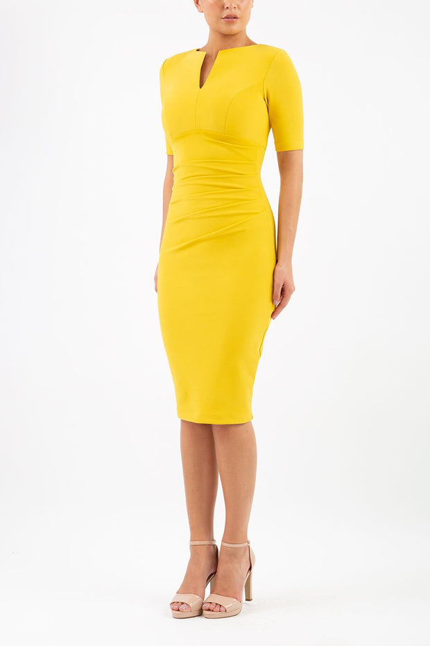 blonde model is wearing diva catwalk lydia short sleeve pencil fitted dress in mustard yellow colour with rounded neckline with a slit in the middle front