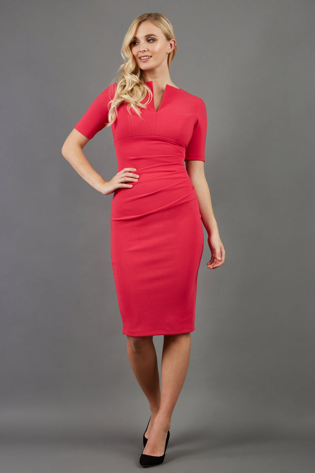 blonde model is wearing diva catwalk lydia short sleeve pencil fitted dress in paradise pink colour with rounded neckline with a slit in the middle front