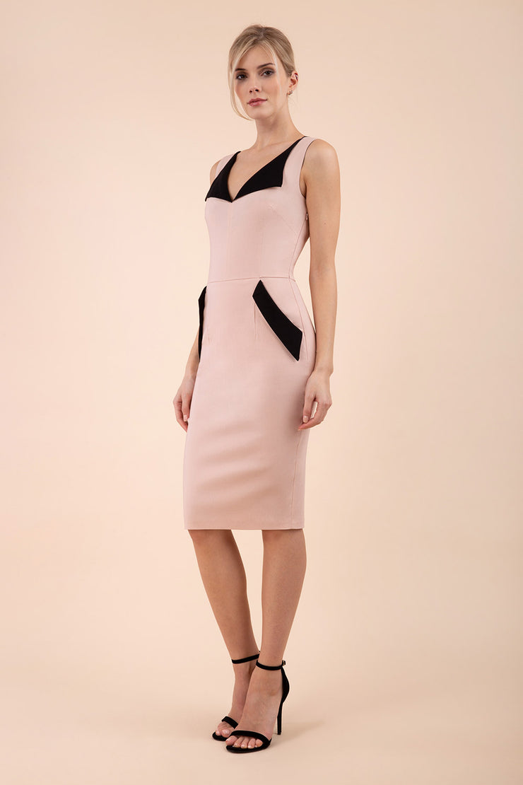 blonde model wearing diva catwalk chevy wiggle pencil dress without sleeves with side pocket detail and lowered v-neckline in nude pink front