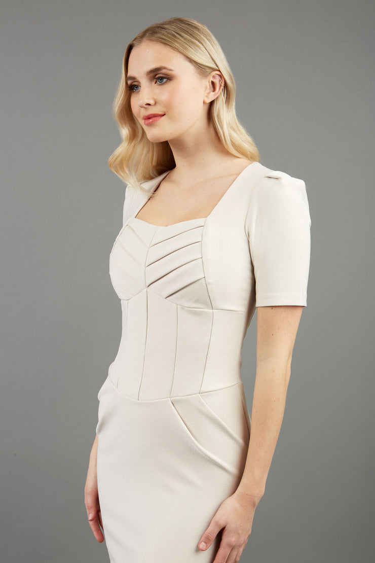 blonde model is wearing diva catwalk seed bonnie pencil skirt dress with cap sleeves and sweetheart neckline with pleating across the tummy in colour ivory front