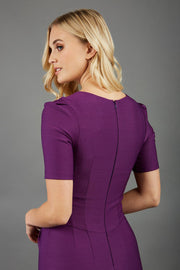 blonde model wearing seed belgravia square neckline purple pencil dress with short pleated sleeves and folded pleating at the front back