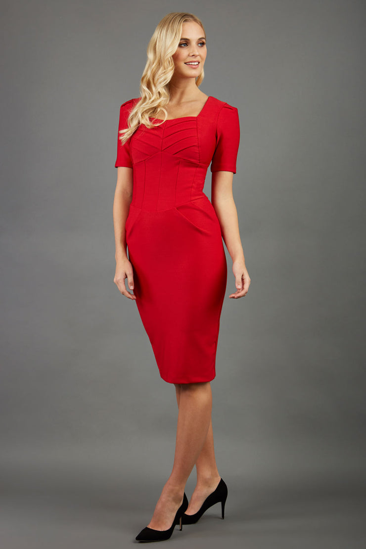 blonde model wearing seed belgravia square neckline red pencil dress with short pleated sleeves and folded pleating at the front