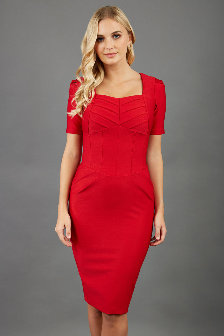 blonde model wearing seed belgravia square neckline red pencil dress with short pleated sleeves and folded pleating like corset band  at the front