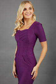 blonde model wearing seed belgravia square neckline purple pencil dress with short pleated sleeves and folded pleating at the front