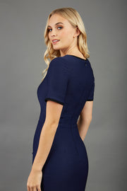 blonde model wearing seed albany contrasted pencil-skirt dress with short sleeves and pleating across the tummy with low square neckline and contrasted detail finishing in navy blue back