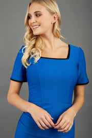 blonde model wearing seed albany contrasted pencil-skirt dress with short sleeves and pleating across the tummy with low square neckline and contrasted detail finishing in sapphire blue front