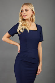blonde model wearing seed albany contrasted pencil-skirt dress with short sleeves and pleating across the tummy with low square neckline and contrasted detail finishing in navy blue front