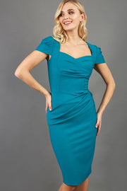 blonde model is wearing diva catwalk seed bonnie pencil skirt dress with cap sleeves and sweetheart neckline with pleating across the tummy in colour harbour blue green front