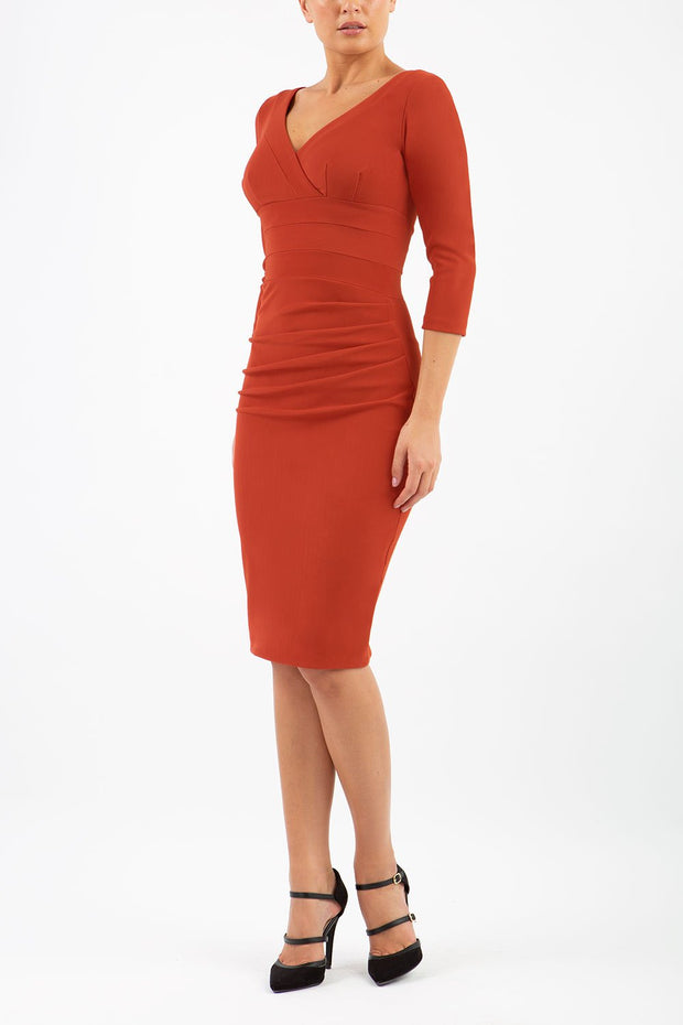 Model wearing the Diva Jemima dress in pencil dress design in terracotta brown front image