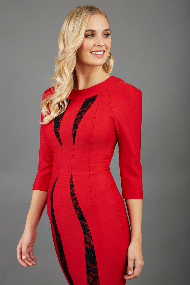 blonde model wearing seed lace red dress with sleeves and rounded necline with lace details pointing towards the band