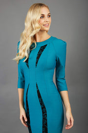 blonde model wearing seed lace blue green dress with sleeves and rounded necline with lace details pointing towards the band front