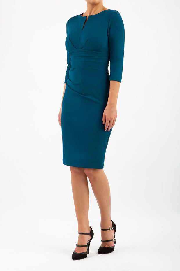 model wearing diva catwalk donna pencil dress in glorious teal colour with wide band and sleeves and rounded neckline with low split in front
