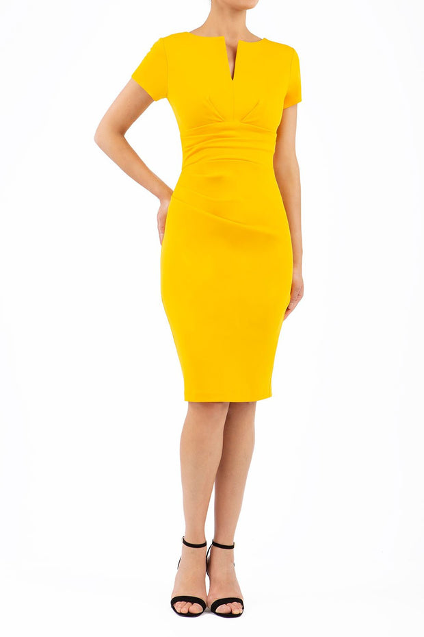 Model wearing Diva Catwalk Donna Short Sleeve Pencil Dress with a wide band and pleating across the tummy area in Saffron Yellow  front
