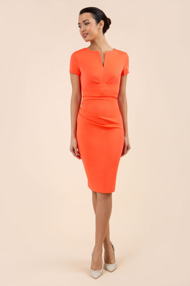 model wearing diva catwalk donna pencil dress in colour hot coral with wide band and sleeves and rounded neckline with low split in front