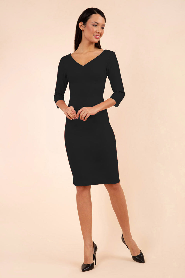 brunette model wearing diva catwalk natalie pencil-skirt dress with sleeves and v-neckline in black front