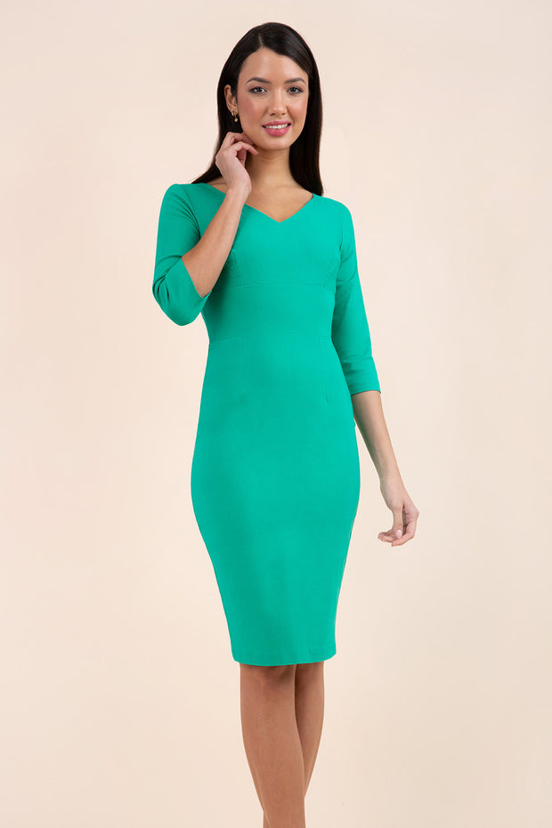 brunette model wearing diva catwalk natalie pencil-skirt dress with sleeves and v-neckline in emerald green front
