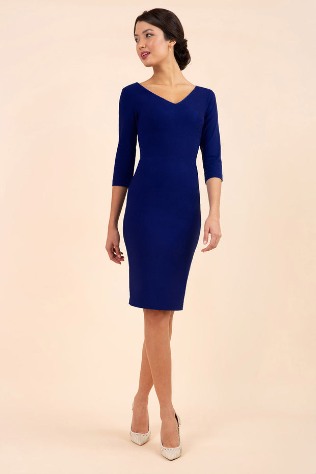 brunette model wearing diva catwalk natalie pencil-skirt dress with sleeves and v-neckline in navy blue front