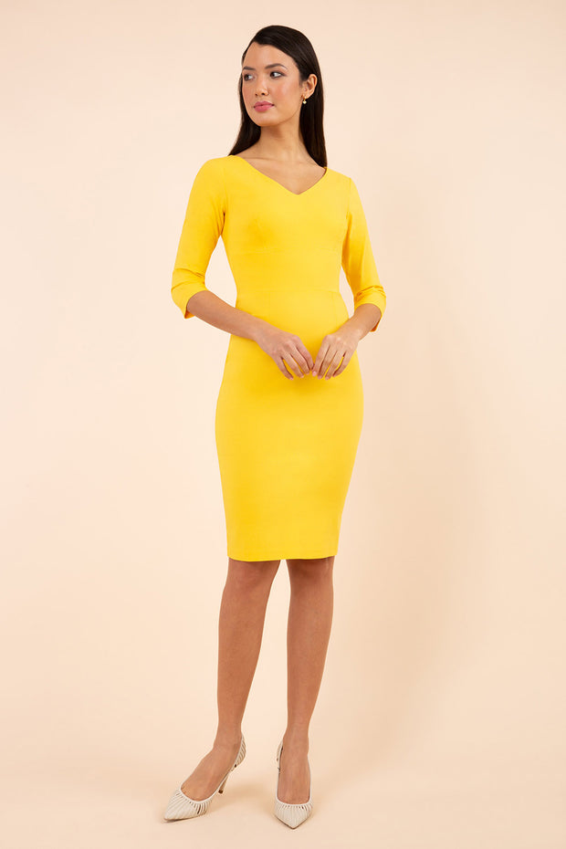 brunette model wearing diva catwalk natalie pencil-skirt dress with sleeves and v-neckline in yellow front