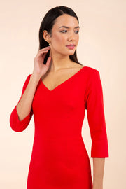 brunette model wearing diva catwalk natalie pencil-skirt dress with sleeves and v-neckline in red front