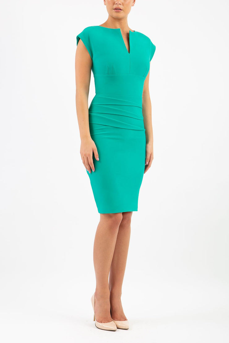 Model wearing the Diva Daphne Pencil with split neckline, sleeveless in emerald green front