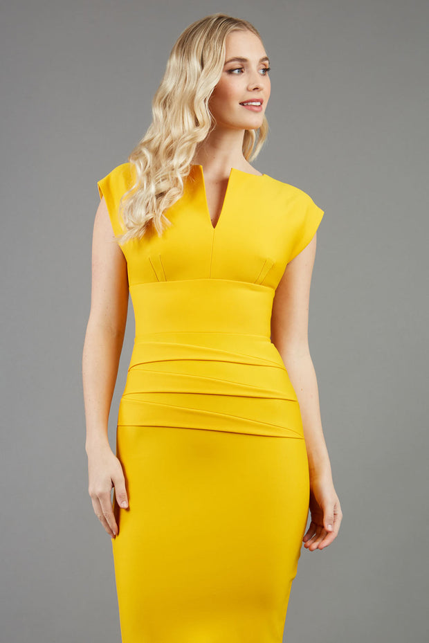 model wearing diva catwalk daphne sleeveless yellow cheap pencil dress with rounded neckline with split in the middle in front