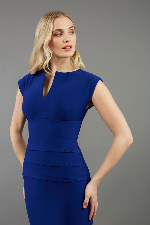 model wearing diva catwalk daphne sleeveless royal blue pencil dress with rounded neckline with split in the middle in front