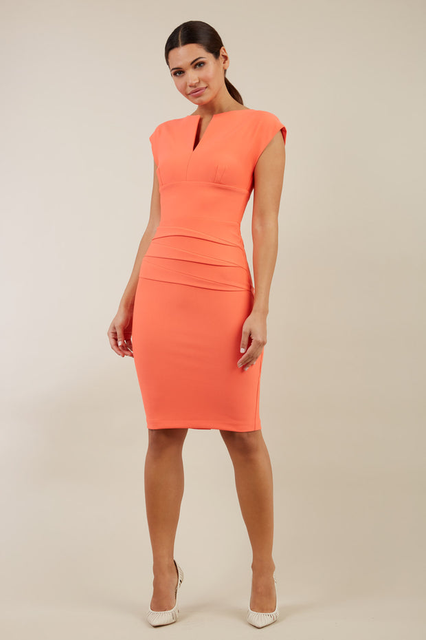 model wearing diva catwalk daphne sleeveless pencil skirt dress with rounded neckline with split in the middle in electric hot coral colour front