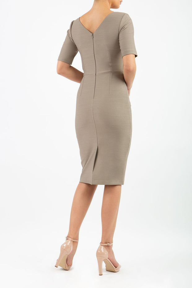 model wearing diva catwalk couture wiltshire fitted pencil-skirt dress with short sleeves and open v-neckline and pleating across the tummy area in taupe brown colour back