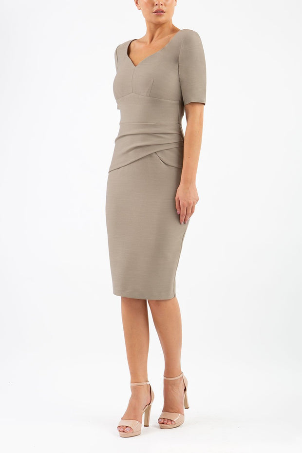 model wearing diva catwalk couture wiltshire fitted pencil-skirt dress with short sleeves and open v-neckline and pleating across the tummy area in taupe brown colour front