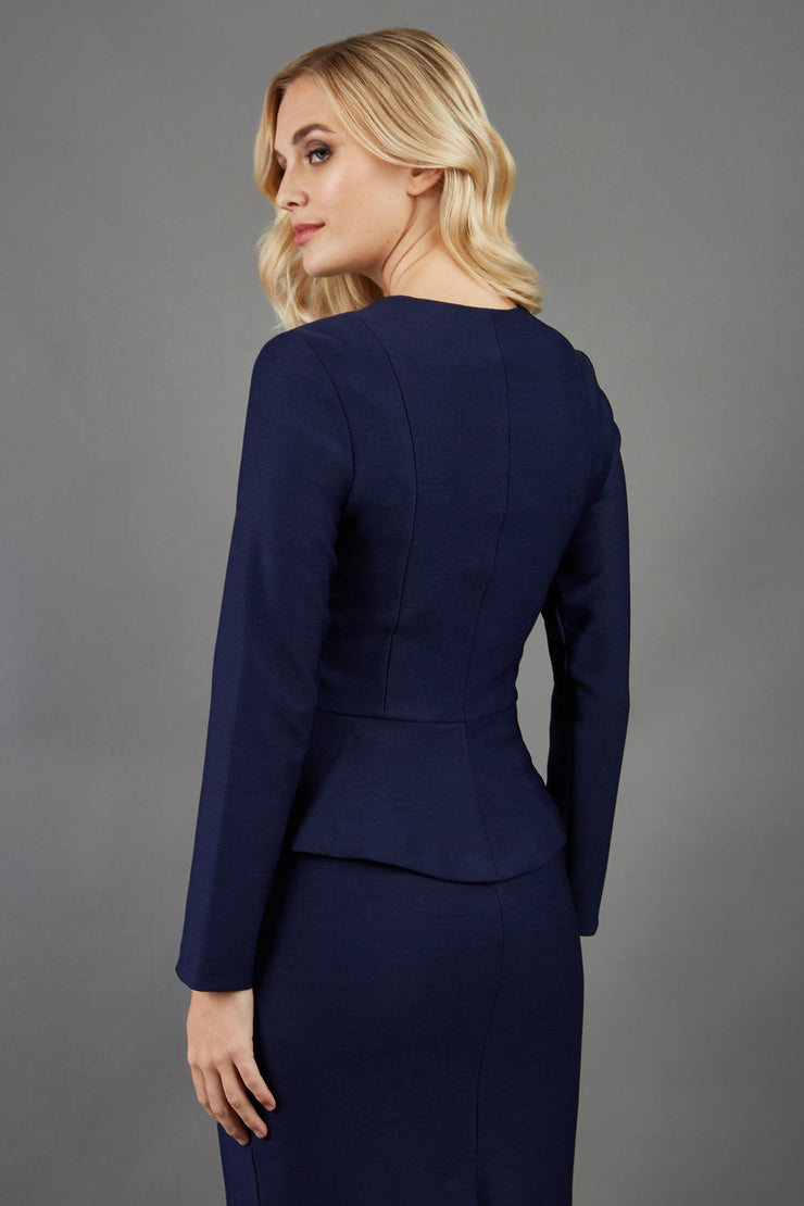 blonde model is wearing seed diva dawlish navy pencil skirt paired with jacket in navy back