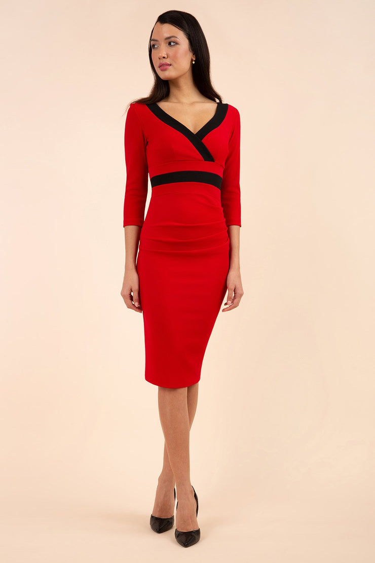 brunette model wearing diva catwalk jemima colour block pencil dress with contrasting low v-neckline and three quarter sleeve in red and black front