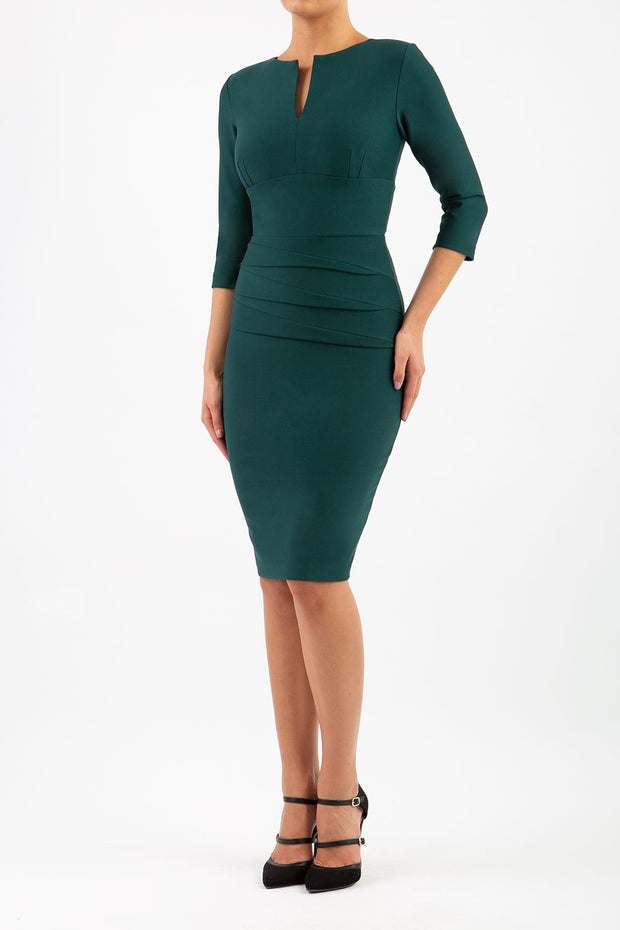 Model wearing the Diva Daphne ¾ Sleeved dress with pleat detail across the hips and ¾ sleeve length in forest green front