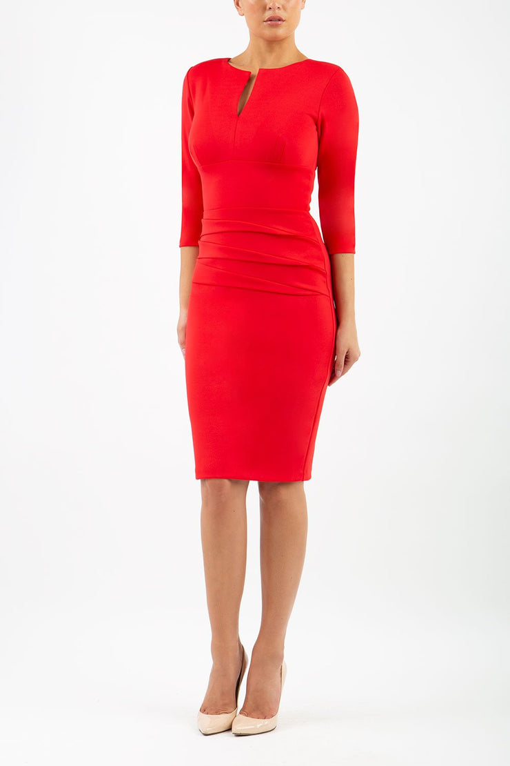 Model wearing the Diva Daphne ¾ Sleeved dress with pleat detail across the hips and ¾ sleeve length in electric red front