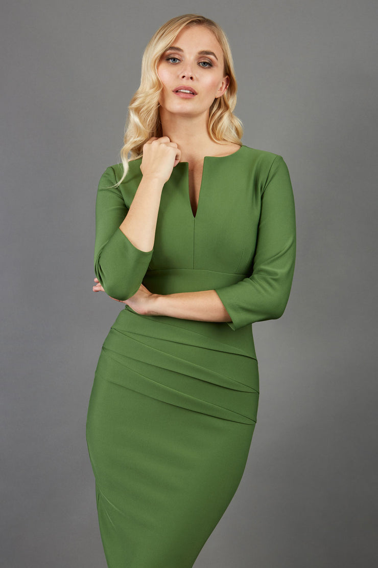 Model wearing the Diva Daphne ¾ Sleeved dress with pleat detail across the hips and ¾ sleeve length in vineyard green front
