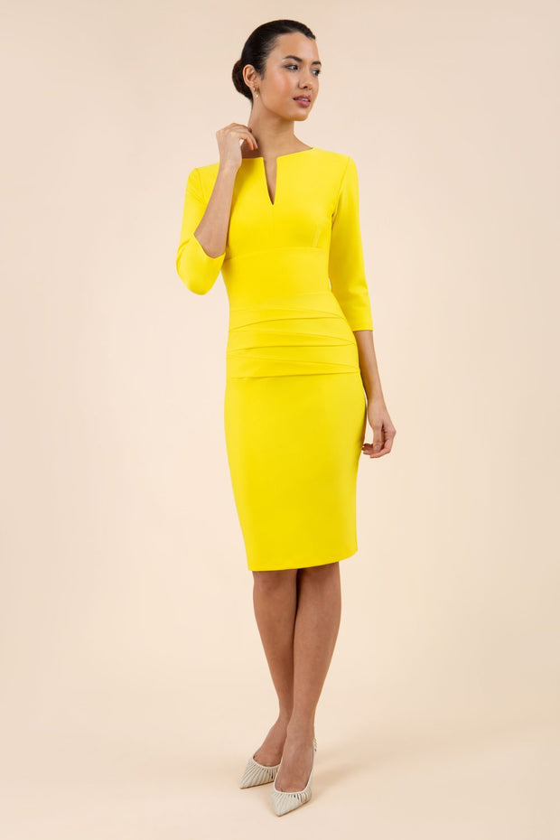 Model wearing Diva catwalk Daphne ¾ Sleeved pencil-skirt dress with pleat detail across the hips and ¾ sleeve length in blazing yellow front