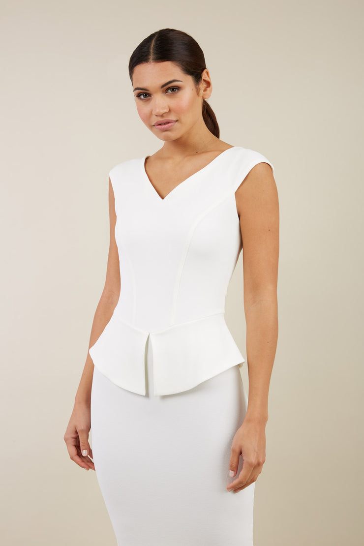 Model wearing the Diva Azalea Peplum dress with semi V neckline and peplum waistline in ivory front image