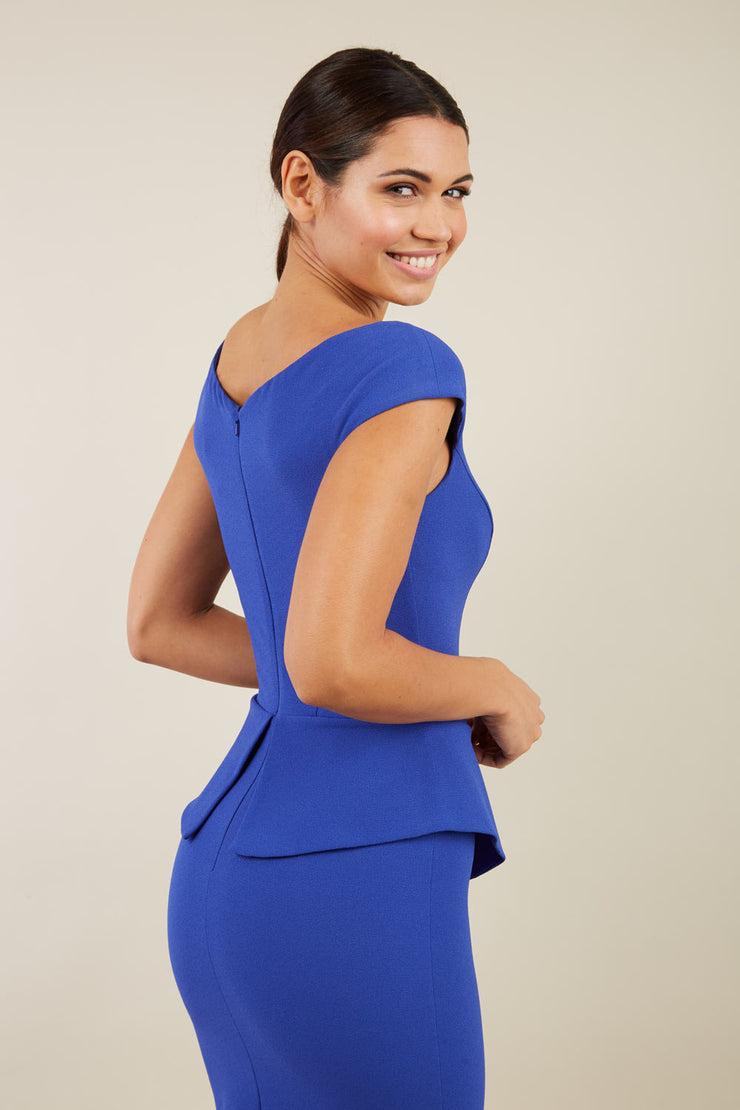 Model wearing the Diva Azalea Peplum dress with semi V neckline and peplum waistline in riviera blue back image