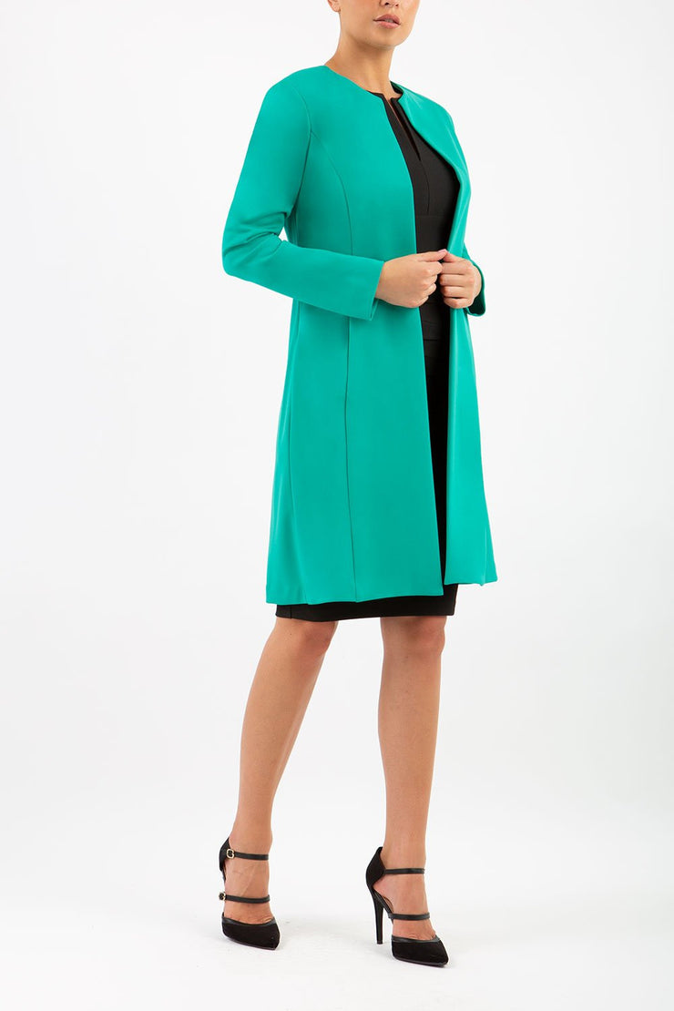 model wearing diva catwalk emerald green coat with long sleeves and a belt front