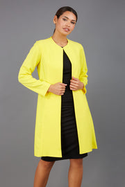 model wearing diva catwalk yellow coat with long sleeves and a belt front