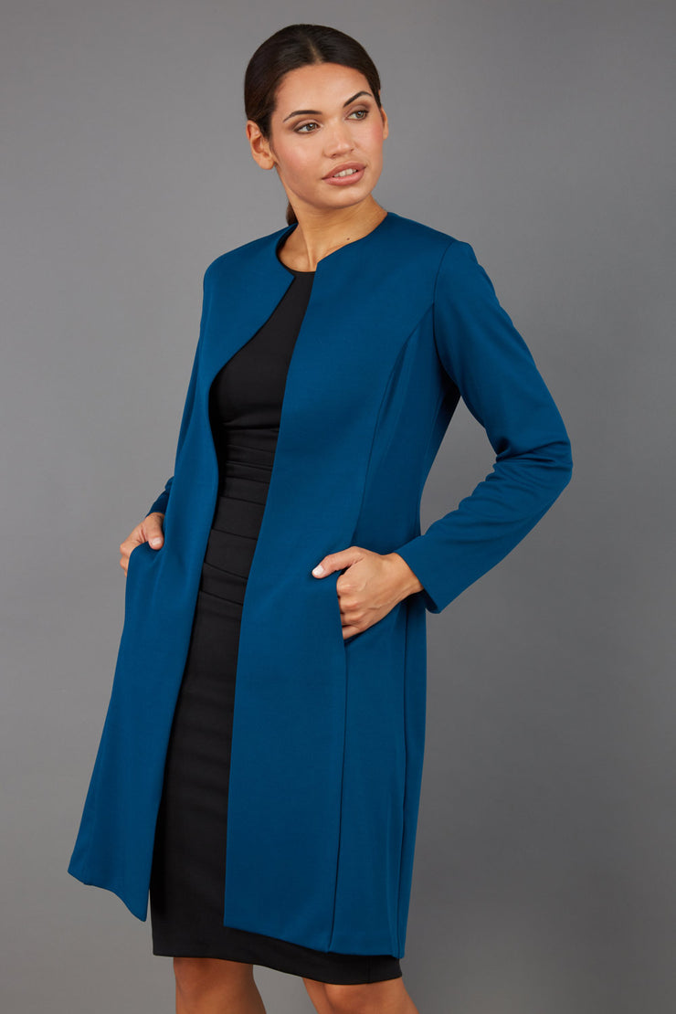 model wearing diva catwalk teal coat with long sleeves and a belt front