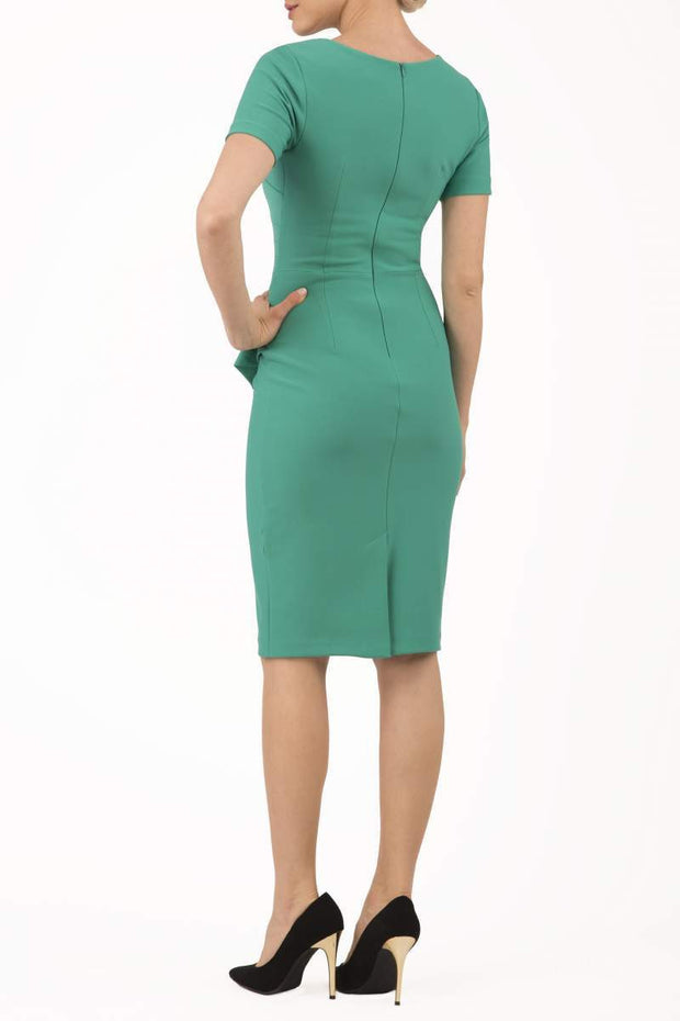 model wearing Diva Catwalk Katia short sleeve dress with an overlapped skirt and pleating across the tummy in emerald green back