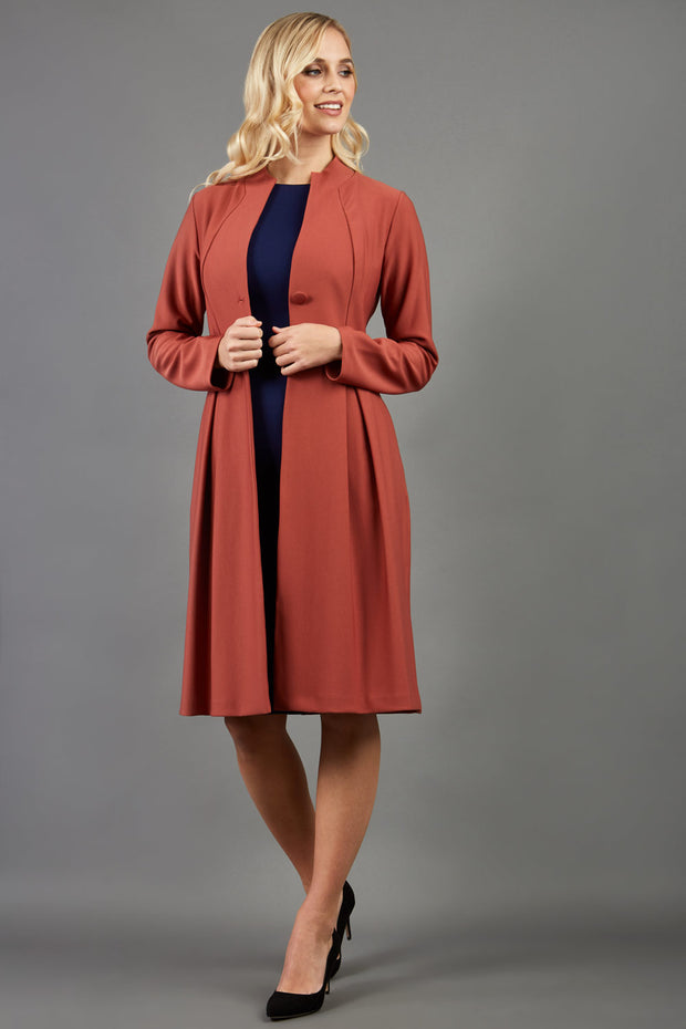 Blonde hair model wearing long sleeve bi stretch Taylor coat in Marsala Brown front image