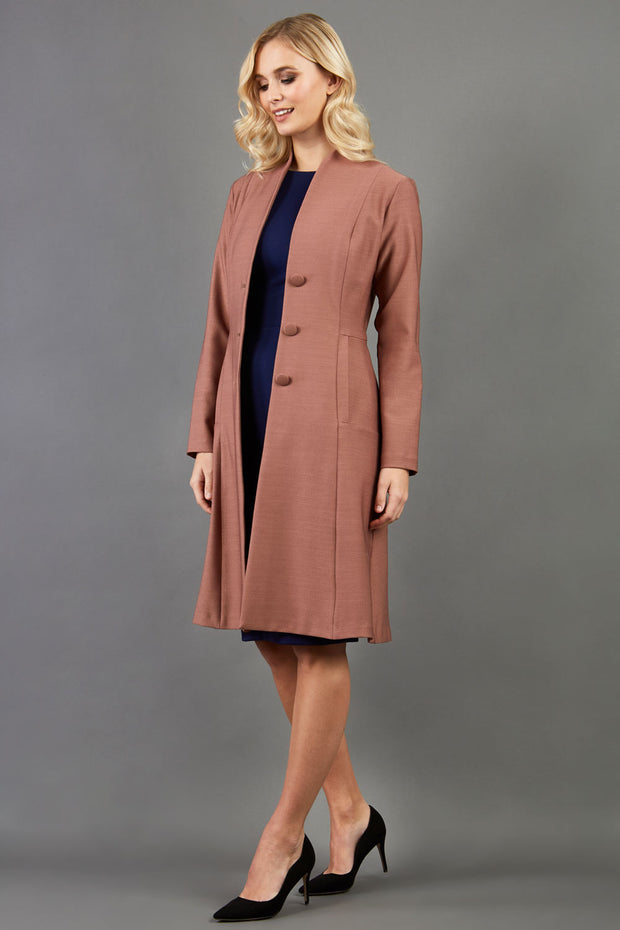 blonde model wearing diva catwalk couture fine raquella coat with buttons across the front and long sleeves with high neck and pockets in acorn brown colour front