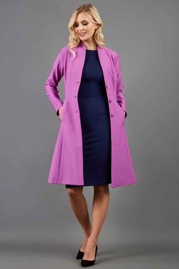 blonde model wearing diva catwalk couture fine raquella coat with buttons across the front and long sleeves with high neck and pockets in magenta mist colour front