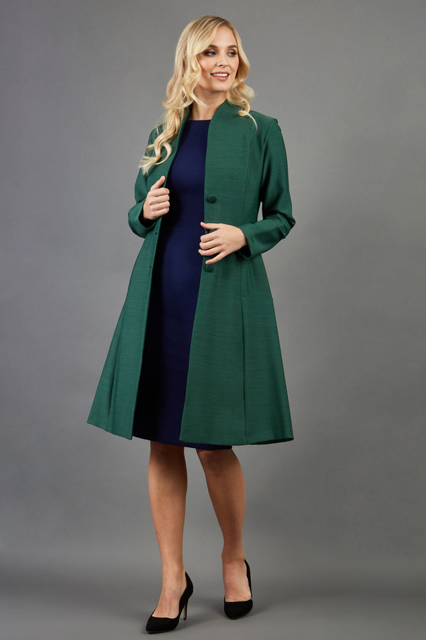 blonde model wearing diva catwalk couture fine raquella coat with buttons across the front and long sleeves with high neck and pockets in chrome green colour front