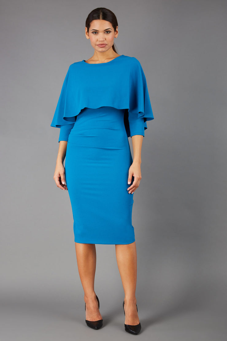 model wearing diva catwalk lizanne pencil-skirt dress with an attached wide cape detail and 3 4 sleeves in colour tropical teal front